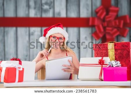 Festive blonde writing her christmas list against festive bow over wood - stock photo