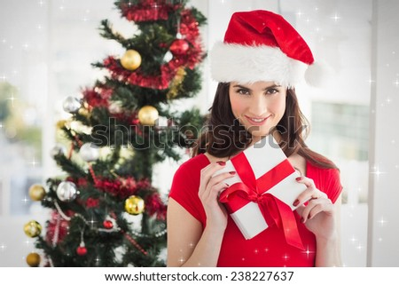 Festive brunette holding gift at christmas against snow - stock photo