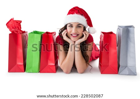 Festive brunette lying near shopping bags on white background - stock photo