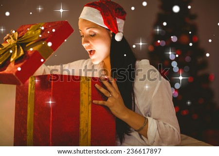 Festive brunette opening a glowing christmas gift against snow - stock photo