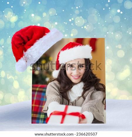 Festive brunette showing gift at christmas against blue abstract light spot design - stock photo