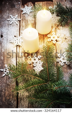 Festive Burning Candles with Christmas Decor Snowflakes and Green Fir Tree on Wooden Background. Vintage style - stock photo