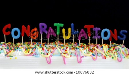 "festive cake with candles spelling ""congratulations"" (no wicks) - stock photo"