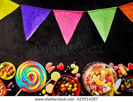 Festive carnival poster with colorful bunting and an assorted of rainbow colored candy as a border over a dark slate background - stock photo