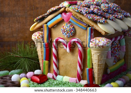 Festive Christmas Gingerbread House decorated with candy canes, marshmallow cones, chocolates and candy in a rustic dark wood setting, closeup with copy space.  - stock photo