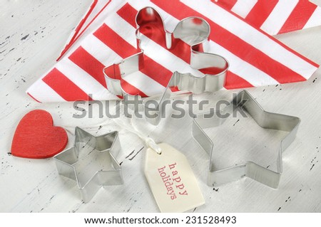 Festive Christmas Holiday background with red and white theme cookie cutters and stripe napkins on vintage shabby chic white wood background. Close up. - stock photo