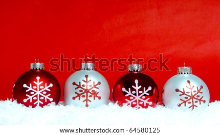 Festive Christmas ornaments resting on snow with a red background - stock photo