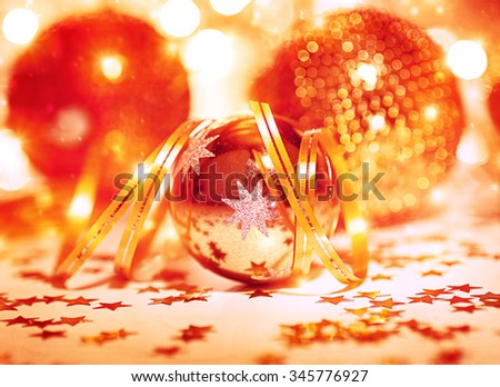 Festive Christmas still life, beautiful golden shiny decorative balls with ribbon and little stars on the table, traditional winter holidays decor - stock photo