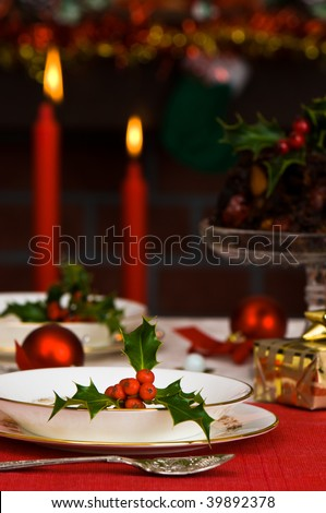 Festive Christmas table setting with lit candles and fireplace in background - stock photo
