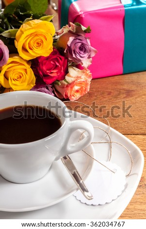 Festive cup of breakfast coffee served black in a white cup with a blank gift tag, a colorful bunch of fresh roses and gift for Valentines, an anniversary, Mothers Day or birthday - stock photo