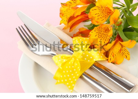 Festive dining table setting with flowers on pink background - stock photo