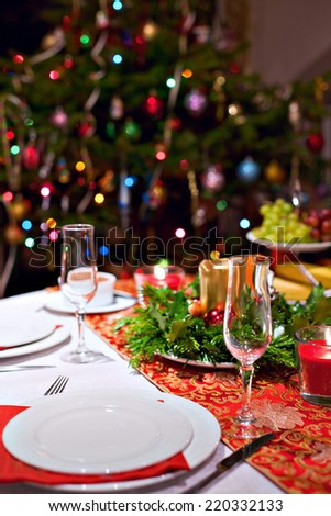 Festive dinner table setting with red table cloth, champagne glasses, candles and Christmas tree on the background - stock photo
