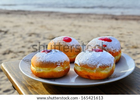Festive donuts with jam on the sandy beach, Eilat, Israel  - stock photo