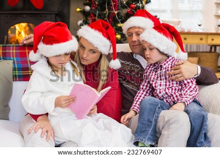 Festive family wearing santa hat while reading on the couch at home in the living room - stock photo
