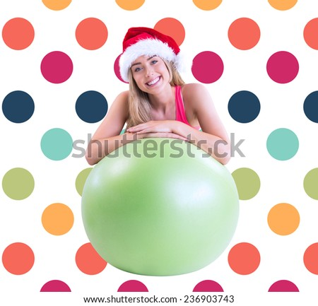 Festive fit blonde posing with exercise ball against colorful polka dot pattern - stock photo