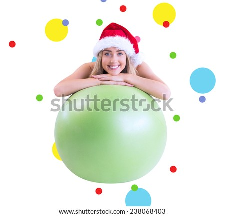 Festive fit blonde posing with exercise ball against dot pattern - stock photo