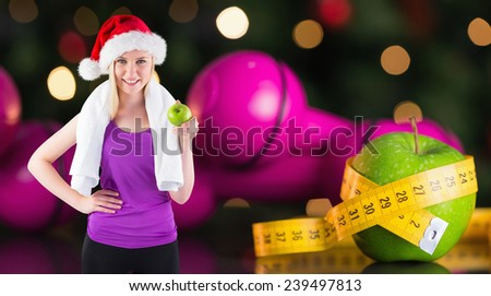 Festive fit blonde smiling at camera holding apple against measuring tape - stock photo