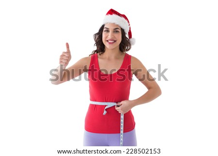 Festive fit brunette measuring her waist on white background - stock photo