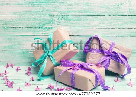 Festive gift boxes and  lilac flowers on turquoise wooden background. Selective focus. Place for text. Toned image. - stock photo