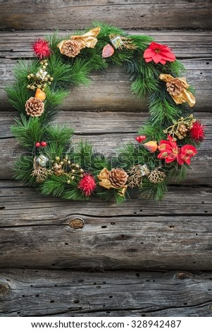 Festive green winter Christmas wreath is at weathered log cabin wall background - stock photo