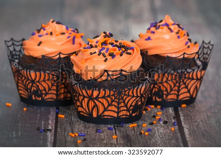 Festive Halloween cupcakes with sprinkles on vintage wooden background, shallow depth of field - stock photo