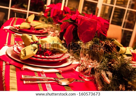 Festive holiday dinner table with plates, glasses and red poinsettias - stock photo