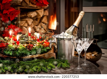 festive home interior decoration for christmas and new year with bottle of champagne and fireplace. candlelight dinner. shiny lights effect - stock photo
