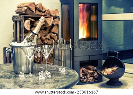 festive home interior wirh champagne, two glasses and fireplace. romantic arrangement. selective focus. retro style toned picture - stock photo