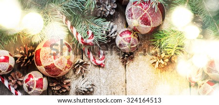 Festive Light with Christmas Vintage Fir Tree Toys, Red Balls, Coniferous, Candy Cane, Pine Cones on Wooden Background - stock photo
