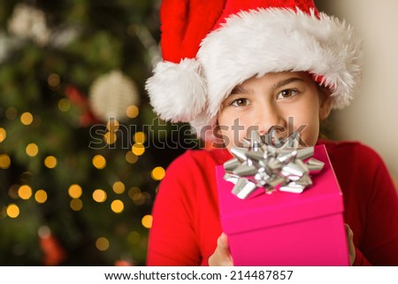 Festive little girl holding a gift at home in the living room - stock photo