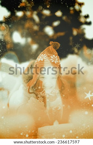Festive little girl in hat and scarf against candle burning against festive background - stock photo