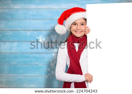 Festive little girl showing card against blurred wooden planks - stock photo