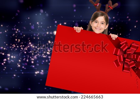 Festive little girl showing card with red christmas ribbon - stock photo