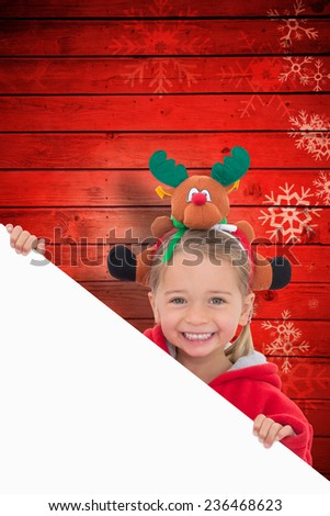 Festive little girl showing poster against snowflake pattern on red planks - stock photo