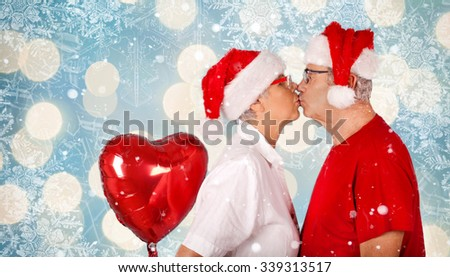Festive mature couple holding a heart balloon against blurred winter Background, Christmas concept - stock photo