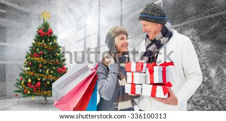 Festive mature couple holding christmas gifts against home with christmas tree - stock photo