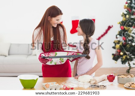 Festive mother and daughter baking together at home at christmas - stock photo