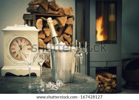 festive New Year's home interior with champagne, antique clock and fireplace - stock photo