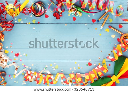 Festive party border or frame of colorful spiral streamers and confetti arranged on a rustic old blue wooden background with a bow tie in the corner and copyspace - stock photo