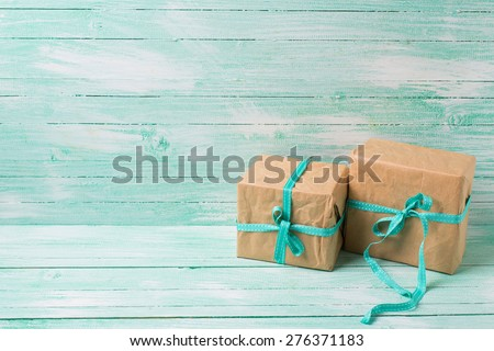 Festive present boxes with ribbon on turquoise painted wooden background. Place for text. Selective focus. - stock photo
