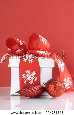 Festive red and white theme Christmas gift box on reflective white table against a red background. Vertical with copy space. - stock photo