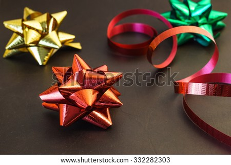 Festive red, green, and golden  ribbon bows close-up as a holiday season symbol - stock photo