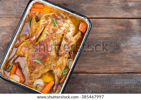 Festive roast duck with vegetables and rosemary on rustic wooden background. Top view - stock photo