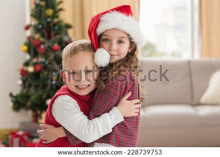 Festive siblings smiling at camera at home in the living room - stock photo
