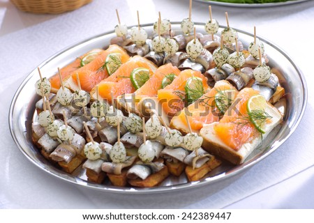 Festive snack with trout sandwiches and canape with fish and onions - stock photo