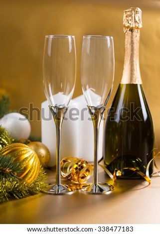 Festive Still Life of Two Elegant Glasses on Golden Background with Bottle of Champagne, White Pillar Candles, and Evergreen Branches Decorated with Gold Christmas Balls and Tinsel Garland - stock photo