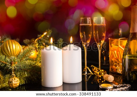 Festive Still Life - Two White Pillar Candles with Burning Wicks on Table with Glasses of Sparkling Champagne and Surrounded with Golden Christmas Decoration Accents in front of Shimmering Background - stock photo