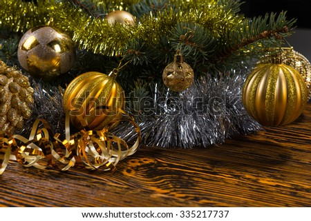 Festive Still Life with Foreground Copy Space - Close Up of Gold Christmas Balls and Metallic Tinsel Garland Hanging on Evergreen Tree Boughs on Rustic Wooden Table - stock photo