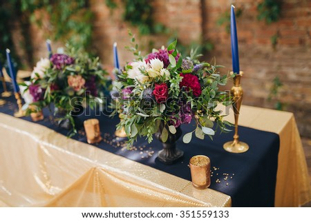 festive table decorated with a tablecloth, candles and floral arrangements from the green, red and white flowers - stock photo