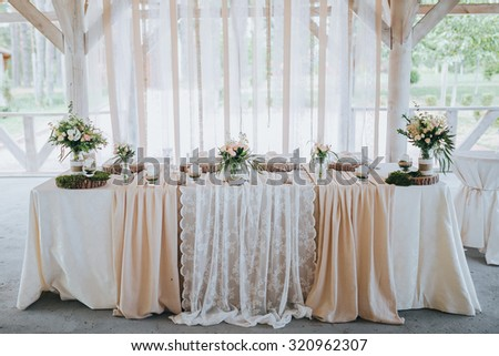 festive table for the bride and groom decorated with cloth and flowers - stock photo